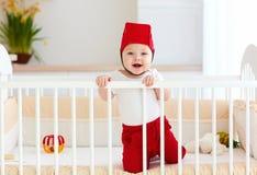 Το αστείο ευτυχές μωρό με το καλάθι παιχνιδιών ως κράνος είναι στην κούνια του Στοκ φωτογραφίες με δικαίωμα ελεύθερης χρήσης
