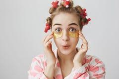 Το αστείο εύθυμο ευρωπαϊκό κορίτσι στα τρίχα-ρόλερ, nightwear και το μάτι επιδιορθώνουν τη μάσκα, εκφράζοντας την έκπληξη ή εντυπ στοκ εικόνα με δικαίωμα ελεύθερης χρήσης