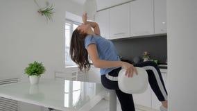 Το αστείο θηλυκό νοικοκυρών που χορεύει και τραγουδά με τα πιάτα στα όπλα μαγειρεύοντας το γεύμα στην κουζίνα στο σπίτι απόθεμα βίντεο