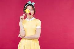 Το αστείο καλό κορίτσι pinup κάλυψε ένα μάτι με το κίτρινο lollipop Στοκ εικόνες με δικαίωμα ελεύθερης χρήσης