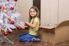 Το αστείο κορίτσι βγάζει ένα χριστουγεννιάτικο δέντρο με τα παιχνίδια Στοκ Φωτογραφίες