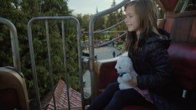 Το αστείο κορίτσι οδηγά σε μια διασταύρωση κυκλικής κυκλοφορίας, χαμογελά και αγκαλιάζει τη teddy αρκούδα της ευτυχώς το φθινόπωρ απόθεμα βίντεο