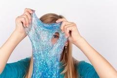 Το αστείο κορίτσι που κρατά ένα μπλε ακτινοβολεί slime μπροστά από το πρόσωπό της και κοίταγμα μέσω της τρύπας του στοκ φωτογραφία με δικαίωμα ελεύθερης χρήσης