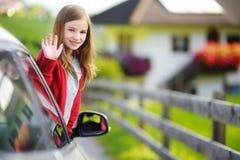 Το αστείο μικρό κορίτσι κολλά το κεφάλι της έξω το παράθυρο αυτοκινήτων κοιτάζοντας προς τα εμπρός για ένα roadtrip ή ένα ταξίδι Στοκ εικόνα με δικαίωμα ελεύθερης χρήσης