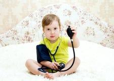 Το αστείο μικρό κορίτσι μετριέται πίεση Στοκ φωτογραφία με δικαίωμα ελεύθερης χρήσης