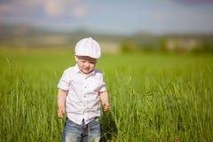 Το αστείο μικρό παιδί στην άσπρη ΚΑΠ χαλαρώνει στην πράσινη χλόη, στο καλοκαίρι PA Στοκ εικόνα με δικαίωμα ελεύθερης χρήσης