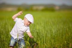 Το αστείο μικρό παιδί στην άσπρη ΚΑΠ χαλαρώνει στην πράσινη χλόη, στο καλοκαίρι PA Στοκ Φωτογραφία