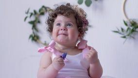 Το αστείο παιδί στο ρόδινο φόρεμα κρατά το λουλούδι και θέτει σε μια σύνοδο φωτογραφιών στο εσωτερικό απόθεμα βίντεο