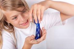 Το αστείο παιχνίδι κοριτσιών με μπλε slime μοιάζει με το gunk στοκ εικόνες