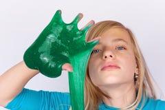 Το αστείο παιχνίδι κοριτσιών με πράσινο slime μοιάζει με το gunk σε ετοιμότητα της στοκ εικόνες