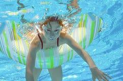 Το αστείο παιδί κολυμπά στη λίμνη κάτω από το νερό, παιδί που έχει τη διασκέδαση και που παίζει με το λαστιχένιο δαχτυλίδι, μικρό Στοκ Φωτογραφία
