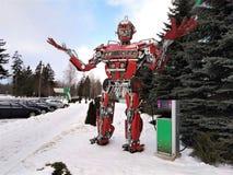 Το αστείο ρομπότ μετάλλων humanoid που το κόκκινο autoboat, αποτελείται από τα ανταλλακτικά αυτοκινήτων, ανεφοδιάζει σε καύσιμα τ στοκ εικόνες