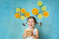 Το αστείο χαμογελώντας κορίτσι πίνει το φρέσκο χυμό Στοκ εικόνες με δικαίωμα ελεύθερης χρήσης