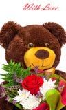 Το αστείο χαμόγελο teddy αντέχει με μια ανθοδέσμη των λουλουδιών Στοκ Εικόνα