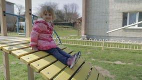 Το αστείο χαριτωμένο κορίτσι παίζει Χαρούμενο κορίτσι που έχει τη διασκέδαση στην παιδική χαρά απόθεμα βίντεο