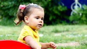 Το αστείο χαριτωμένο κορίτσι παιδιών παίζει σε μια φωτογραφική διαφάνεια φιλμ μικρού μήκους