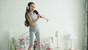 Το αστείο χαριτωμένο μικρό κορίτσι στο ασύρματο τραγούδι χορού ακουστικών με τη χτένα και έχει τη διασκέδαση το πρωί διακοπών που φιλμ μικρού μήκους