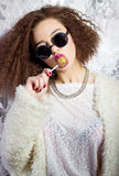 Το αστείο όμορφο προκλητικό κορίτσι στα γυαλιά και ένα άσπρο παλτό γλείφει έναν φραγμό καραμελών, φωτεινό makeup, στούντιο φωτογρ Στοκ Εικόνες