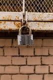Το αστικό ύφος σχεδίου grunge άρθρωσε αρθρωμένο το μέταλλο ξεπερασμένο κλειδαριά ευμετάβλητο χρώμα γκρίζο στο υπόβαθρο τουβλότοιχ στοκ εικόνες