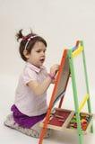Το λατρευτό μικρό κορίτσι επισύρει την προσοχή στο μαύρο πίνακα με την κιμωλία Στοκ Εικόνες