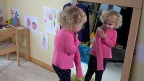 Το λατρευτό παιδί ανεπιτυχές προσπαθεί στα ενδύματα undress μπροστά από τον καθρέφτη απόθεμα βίντεο