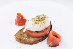 Το αυγό κυνήγησε λαθραία με τα ψάρια και την ντομάτα σολομών Στοκ φωτογραφία με δικαίωμα ελεύθερης χρήσης