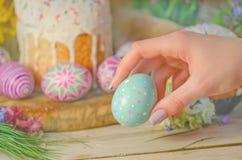 Το αυγό Πάσχας σε ένα χέρι σε ένα υπόβαθρο της διακόσμησης και της άνοιξη Πάσχας ανθίζει Έννοια προγευμάτων Πάσχας Στοκ εικόνες με δικαίωμα ελεύθερης χρήσης