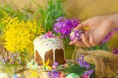 Το αυγό Πάσχας σε ένα χέρι σε ένα υπόβαθρο της διακόσμησης και της άνοιξη Πάσχας ανθίζει Έννοια προγευμάτων Πάσχας Στοκ Εικόνα
