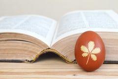 Το αυγό Πάσχας χρωμάτισε φυσικά και παλαιό βιβλίο στοκ εικόνες