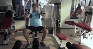 Το αυξημένο άτομο στη γυμναστική εκτελεί το θωρακικό Τύπο ασκήσεων απόθεμα βίντεο