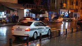 Το αυτοκίνητο της της Γεωργίας αστυνομίας με τις συμπεριλαμβανόμενες δαπάνες αναλαμπτήρων τη νύχτα στην οδό πόλεων απόθεμα βίντεο