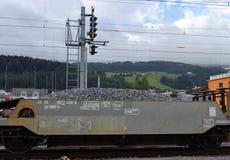 Το αυτοκίνητο χοανών έρματος διαδρομής, αμμοχάλικο γέμισε το αυτοκίνητο φορτίου σιδηροδρόμου, που περνά το σήμα Στοκ Εικόνα
