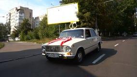 Το αυτοκίνητο Newlyweds οδηγά την οδό σε μια θερινή ημέρα απόθεμα βίντεο