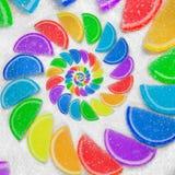 Το αφηρημένο σπειροειδές ουράνιο τόξο ζελατίνας φρούτων ενσφηνώνει τις φέτες στο υπόβαθρο άμμου άσπρης ζάχαρης Καραμέλες ζελατίνα Στοκ φωτογραφία με δικαίωμα ελεύθερης χρήσης