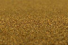 Το αφηρημένο υπόβαθρο γοητείας ακτινοβολεί χρυσά μόρια στοκ εικόνα