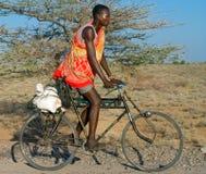 Το αφρικανικό άτομο στα παραδοσιακά ενδύματα οδηγά ένα ποδήλατο στοκ φωτογραφία