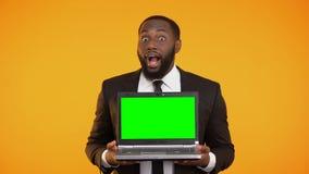 Το αφροαμερικανός αρσενικό στην επίσημη εκμετάλλευση κοστουμιών το lap-top και το χαμόγελο, wow απόθεμα βίντεο