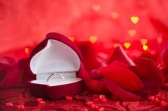Το δαχτυλίδι αρραβώνων και κόκκινος αυξήθηκε πέταλα Στοκ φωτογραφία με δικαίωμα ελεύθερης χρήσης