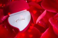 Το δαχτυλίδι αρραβώνων και κόκκινος αυξήθηκε πέταλα Στοκ εικόνα με δικαίωμα ελεύθερης χρήσης