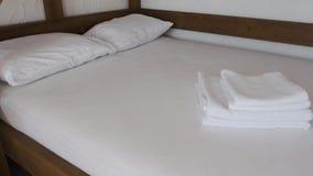 Το Α δύο-το κρεβάτι με τα άσπρα και καθαρά φύλλα και τα μαξιλάρια στέκονται σε ένα δωμάτιο ξενοδοχείου απόθεμα βίντεο