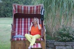 Το Α η ψάθινη καρέκλα παραλιών, η ελκυστική γυναίκα με ένα κοστούμι λουσίματος και ένα κινητό τηλέφωνο, εδώ χρονικές στάσεις ακόμ στοκ φωτογραφία με δικαίωμα ελεύθερης χρήσης