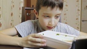 Το Α το καυκάσιο αγόρι που τρώει το chineese γρήγορο φαγητό, στιγμιαία νουντλς από το μίας χρήσης εμπορευματοκιβώτιο στο σπίτι, τ απόθεμα βίντεο