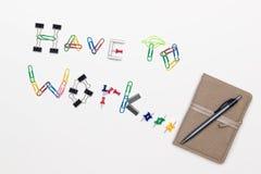 Το Α πρέπει να λειτουργήσει κείμενο φιαγμένο από συνδετήρες και καρφίτσες, και ένα σημειωματάριο με μια μάνδρα σε ένα φωτεινό υπό Στοκ Εικόνες