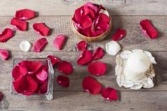 Το βάζο γυαλιού και το ξύλινο τόξο γέμισαν με τα κόκκινα ροδαλά πέταλα, άσπρο αρωματικό κερί βανίλιας Ξύλινη ανασκόπηση aromather Στοκ Εικόνα