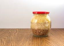 Το βάζο γυαλιού με το μίγμα των κόκκων έκλεισε την κόκκινη ΚΑΠ επάνω Στοκ Εικόνες