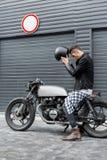 Το βάναυσο άτομο κάθεται στη μοτοσικλέτα συνήθειας δρομέων καφέδων στοκ εικόνες