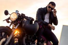 Το βάναυσο άτομο κάθεται στη μοτοσικλέτα συνήθειας δρομέων καφέδων στοκ φωτογραφίες με δικαίωμα ελεύθερης χρήσης