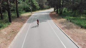 Το βέβαιο κατάλληλο κορίτσι οδηγά ένα ποδήλατο που φορά τη ρόδινη εξάρτηση και το μαύρο κράνος Έννοια Triathlon φιλμ μικρού μήκους