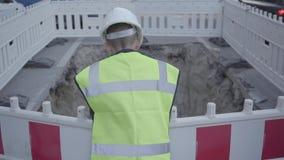 Το βέβαιο μικρό αγόρι που φορούν τον εξοπλισμό ασφάλειας και το κράνος κατασκευαστών που στέκονται στο δρόμο και οι έλεγχοι κοιλα απόθεμα βίντεο