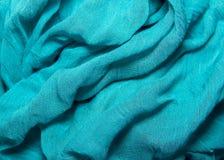 το βαμβάκι και το μετάξι σύστασης υφάσματος τσαλάκωσαν τις μπλε πτυχές που βρίσκονται σε ένα TA Στοκ Φωτογραφίες